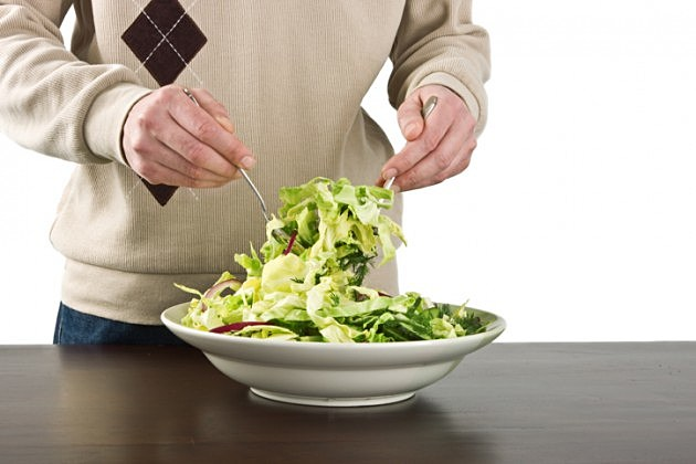 Man mixing fresh salad