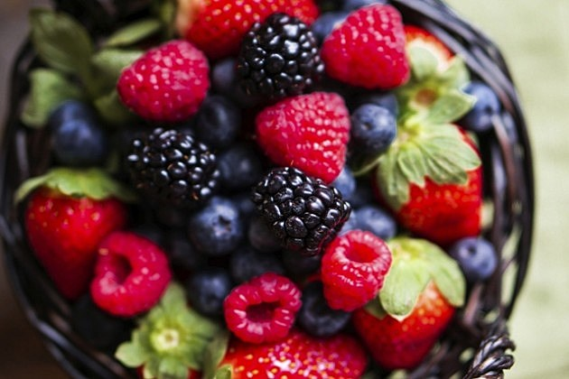 Mix of fresh berries in a basket on wooden background