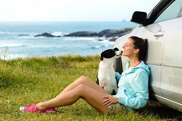Dog licking woman's face by car in front of ocean